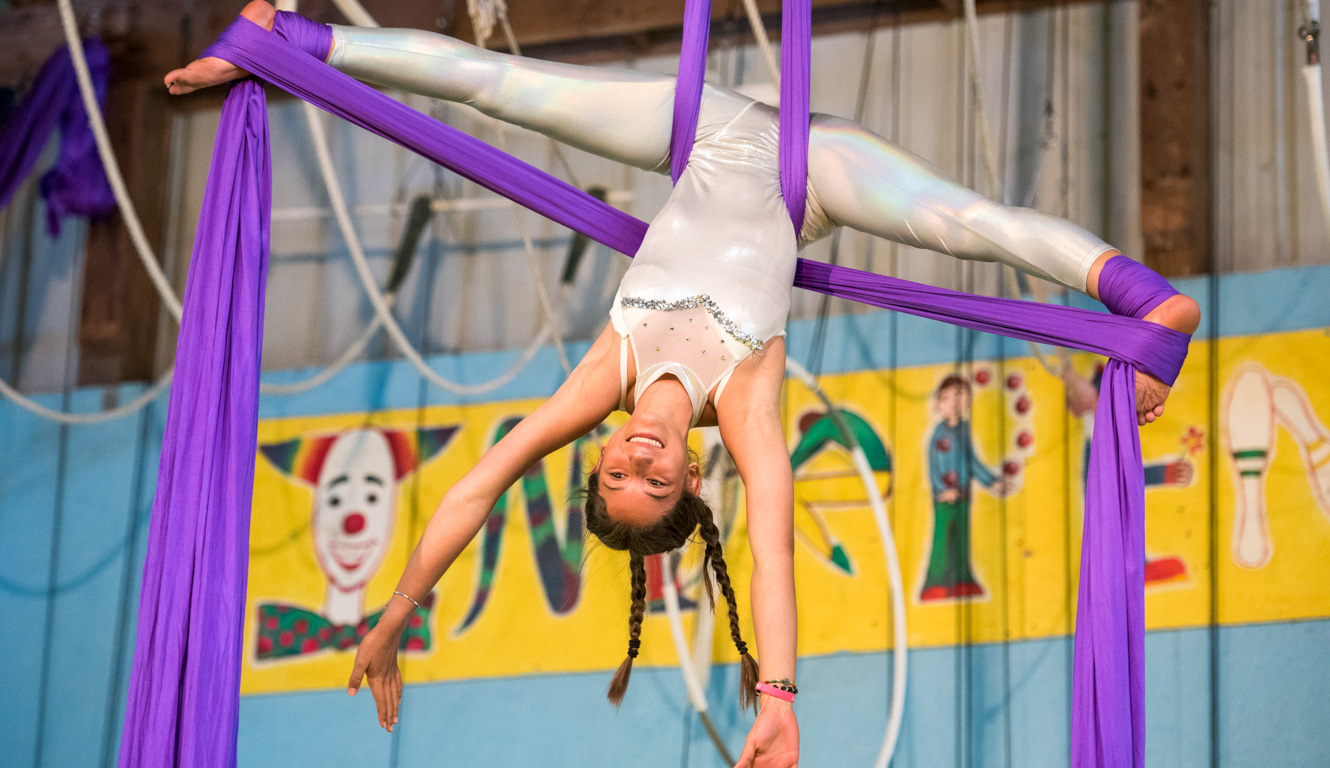 Girl performs on aerial silks at summer camp