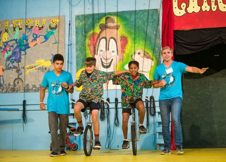 Staff members help campers on unicycles