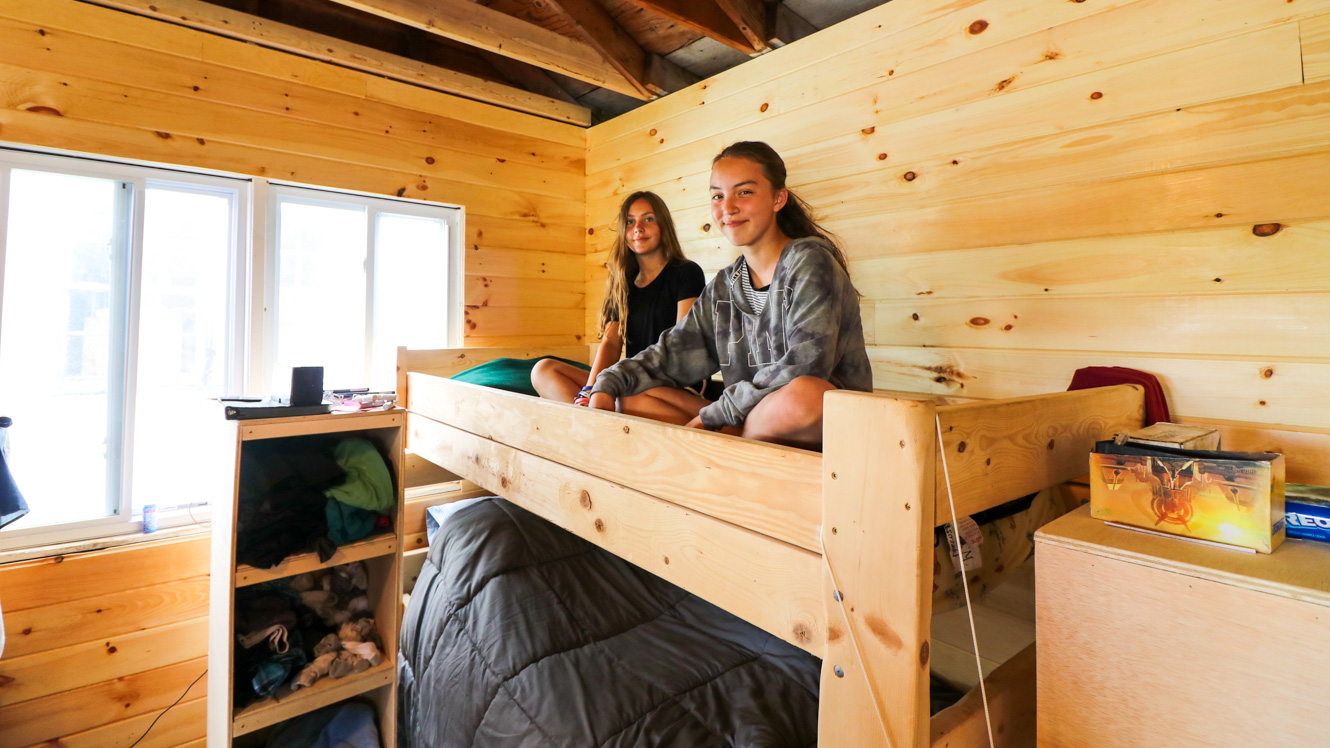 Girls hang out on camp cabin bunk