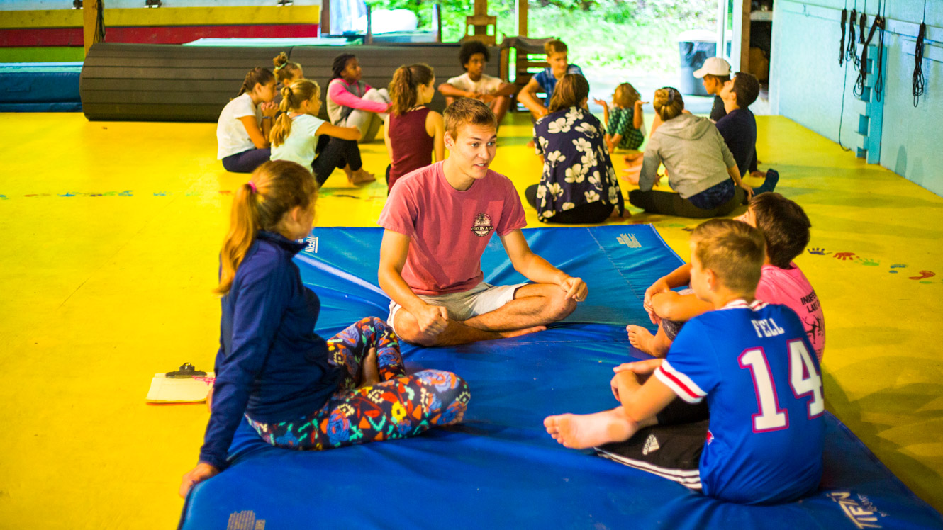 Staff member sits with campers on mat