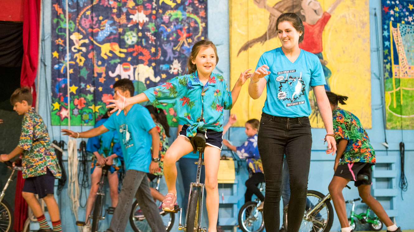 Circus staff helps camper on unicycle
